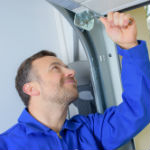 Repair man going through garage door repair the most common problems checklist